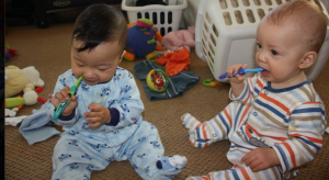 Twin babies brushing teeth